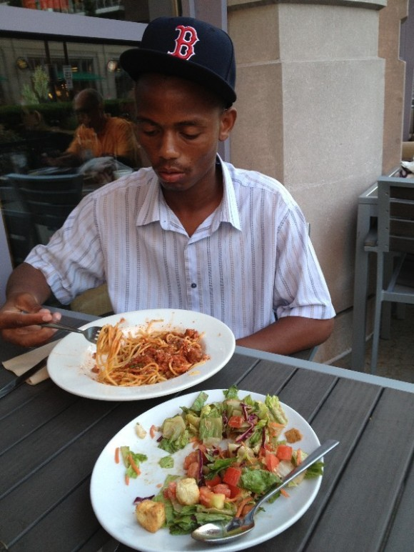 """Dinner at an outdoor cafe after our first day in Boston -- where he had to buy a """"B"""" cap so he could fit in. A Facebook post where he gloated to friends back in the SA winter about eating outdoors on a summer evening."""